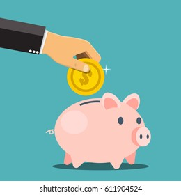 Businessman hand putting a coin into a piggy bank. Saving and investing money concept.
