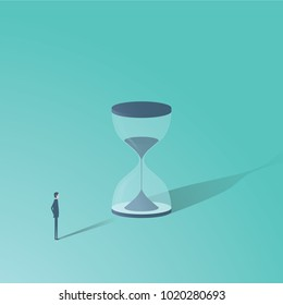 Businessman looking at hourglass vector minimalist concept. Time is money symbol, project management, deadlines etc. Eps10 vector illustration.