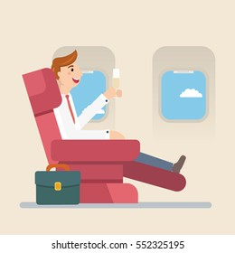 Businessman or manager sitting in an airplane in business class. Man drinking champagne.