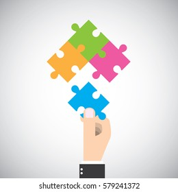 Businessman put one jigsaw piece to complete big picture. Four cooperation vector graphic design.