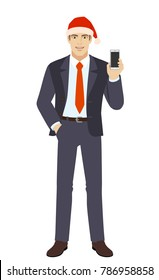 Businessman in Santa hat with hand in pocket and with mobile phone. Full length portrait of businessman in a flat style. Vector illustration.