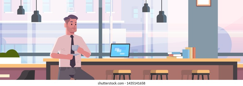 businessman sitting on chair at bar counter with laptop coffee break concept business man drinking cappuccino modern cafe interior flat portrait horizontal