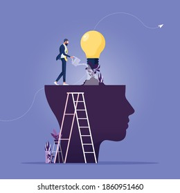 Businessman watering that growing lightbulb plant from the brain as metaphor growth personality