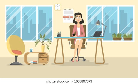 Businesswoman at office sitting at desk and smiling.