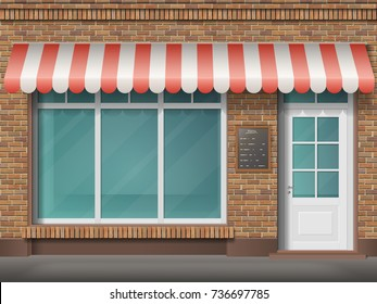 Cafe or store front with large transparent window and awning. Facade of red brick. Empty glass showcase of boutique. Entrance in the small  shop.