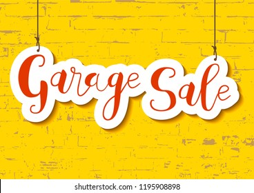 calligraphy lettering of garage sale in orange in paper cut style on yellow textured brick wall