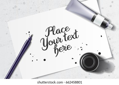 Calligraphy mockup with brush pen and black ink bottle on the background of white sheet of paper and grunge table