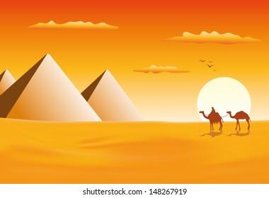 Camel caravan at pyramids in sunset