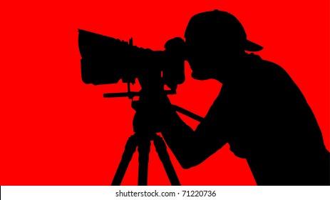 cameraman looking through movie camera on a tripod