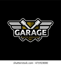 Car service auto repair  Logo emblem badge. The keys and the word Garage in the background of the shield with wings