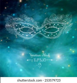 Card with festive venetian mask on blurred glowing background. Elements of this image furnished by NASA.