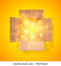 Cardboard box with a bright glow inside. Open box. Top view. Detailed bokeh effect.