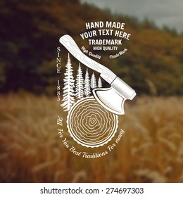 carpenter craft style background with axes hack the round trunk and spruce tree back middle label on forest and field blur photo