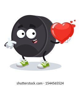 cartoon black rubber hockey puck character mascot keeps the heart on white background