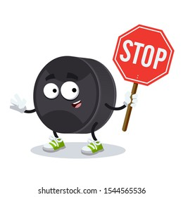 cartoon black rubber hockey puck mascot with tablet stop in hand on white background