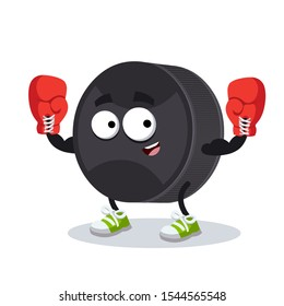 cartoon black rubber hockey puck mascot in red boxing gloves on white background