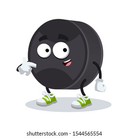 cartoon black rubber hockey puck mascot showing himself on a white background