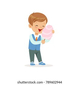 Cartoon cheerful boy eating sweet cotton candy on stick. Kid character with brown hair dressed in shirt, vest and jeans. Colorful flat vector design