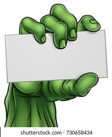 A cartoon green zombie Halloween monster claw hand holding blank paper sign or card