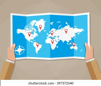 Cartoon hands hold folded paper map of world with color point markers. World map countries. vector illustration in flat design on brown background