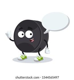 cartoon joyful black rubber hockey puck mascot with a speech bubble on a white background