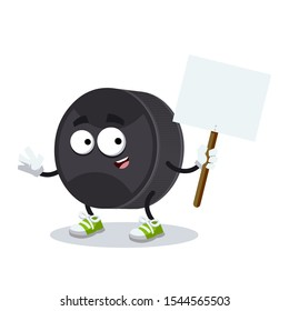 cartoon joyful black rubber hockey puck mascot with tablet in hand on white background