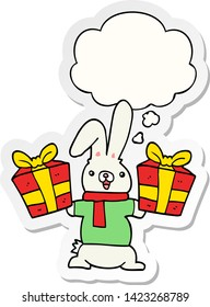 cartoon rabbit with christmas presents with thought bubble as a printed sticker