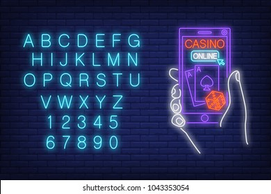 Casino online neon sign. English alphabet and numbers. Hand holding smartphone with dice and playing cards. Night bright advertisement. Vector illustration in neon style for internet gambling and luck
