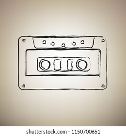 Cassette icon, audio tape sign. Vector. Brush drawed black icon at light brown background.