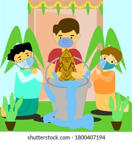 Celebrating Eco-friendly Ganesha festival, Boys doing immersed of Hindu God Ganesha to the bucket at infront of home with wearing surgical mask due to pandemic of coronavirus, covid-19.