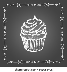 Chalk cupcake and vintage frame on gray background.