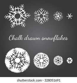Chalk drawn on black board snowflakes of different size and level of detail. New year, Christmas graphic elements, templates for design. Brush drawn snow crystals of various type with rough edges.