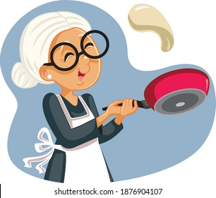 Cheerful Grandmother Flipping Pancakes for Breakfast. Senior woman cooking dessert meal with special recipe