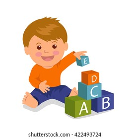 Cheerful toddler sitting collects a pyramid of colored cubes. Concept development and education of young children.