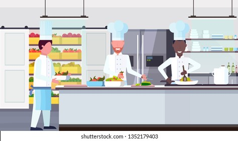 chef cook carrying plate with meal ingredients mix race workers cooking food culinary teamwork concept modern commercial restaurant kitchen interior horizontal flat