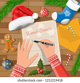 Child hand pen writing letter to santa claus. Wooden desk candycane, envelope, fur branches, holly, stocking, hat, gingerbread man. Christmas new year eve xmas holidays. Vector illustration flat style