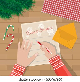 Child Hand with pen Writing letter to santa claus. wooden desk with candycane, envelope and fur branches. wishes on christmas and new year eve. vector illustration