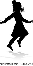A child in silhouette playing in Christmas or winter cold weather clothing
