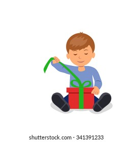 The child sits on the floor and opens a box with a gift.