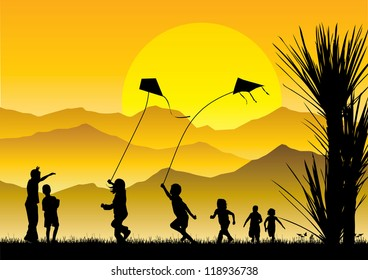 Children flying kites silhouette at sunset