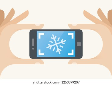 Children photographer hand holding mobile phone and taking photo of snowflake. Winter, New Year and Christmas holidays, photography, technology, creativity, art concepts