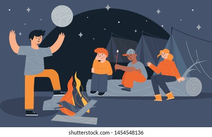 Children sitting near a campfire and tents eating marshmallow and telling scary stories at night. Camping trip, backpacking, and traditional bonfires in scout camp. Kids summer camp outdoor activity.