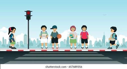 Children waiting for the traffic light to cross the crosswalk.