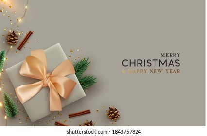 Christmas background. Design with 3d Xmas decoration objects, gift box, fir branches, pine cones, shiny glitter confetti, garland lights. Flatlay top view composition. Greeting card, banner, poster.