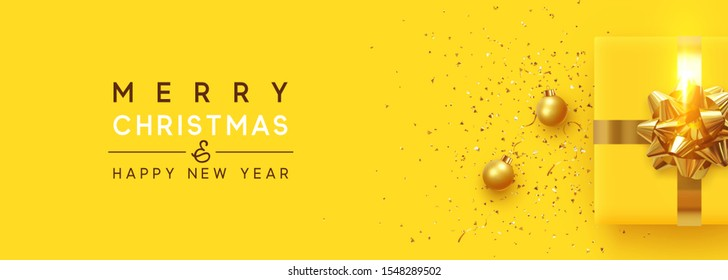 Christmas background. Realistic yellow gift boxes, with shiny golden confetti, Xmas balls, decorative baubles. Flat lay, top view. Horizontal Festive New Year poster, greeting cards, headers, website.