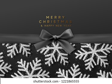 Christmas background with shining silver snowflakes and a black ribbon with bow.