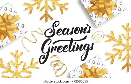 Christmas. Background for winter seasonal holidays. Gold glitter snowflakes, gift boxes and Lettering Season's Greetings