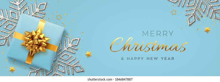 Christmas banner. Realistic blue gift box with golden bow, silver shining snowflake, gold stars and glitter confetti. Xmas background, horizontal poster, greeting cards, headers website. Vector.