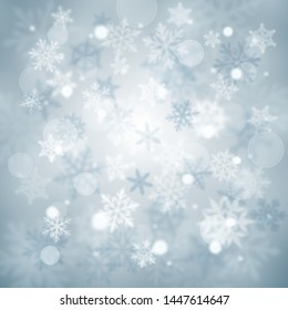 Christmas blurred background of complex defocused big and small falling snowflakes in light blue colors with bokeh effect