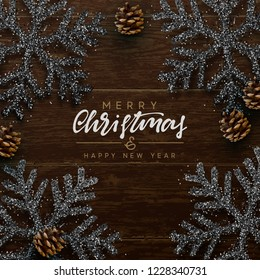 Christmas composition on wooden background. Xmas decoration design, snowflake color black, pine cone. Brown realistic Wood texture. Flat lay, top view.